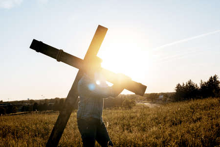 A closeup shot of a male carrying a wooden cross with the sun shining in the background