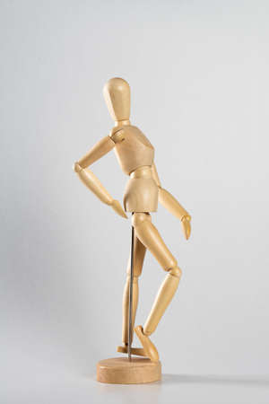 A vertical shot of a wooden pose doll walking with one hand on its waist on a white background Stock Photo