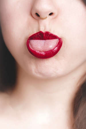 A vertical closeup shot of a female with red lipstick showing her tongue - great for a fashion blog post