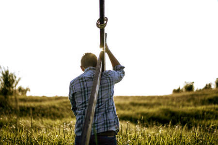 A male carrying a hand made wooden cross in a grassy field shot from behind