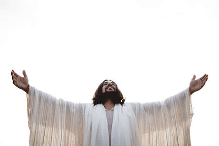 A shallow focus shot of Jesus Christ with his hands and head up towards the sky