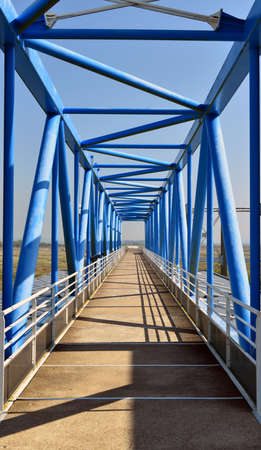 A vertical shot of a bridge with blue poles on a sunny day