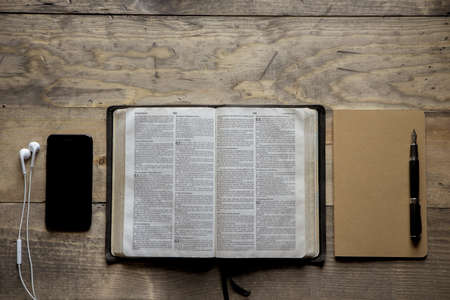 An overhead shot of opened bible in the middle of a notebook and a smartphone on a wooden surface