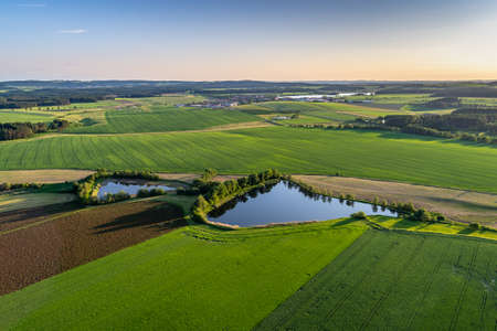 A bird's-eye shot of breathtaking green fields with small ponds in a rural area. Perfect for rural scenarios.