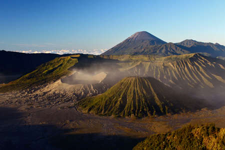 A horizontal shot of the beautiful Bromo volcano covered in fog under the clear sky