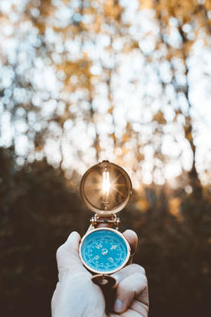 A vertical shot of a person holding a compass with the sun shining through the hole and blurred background