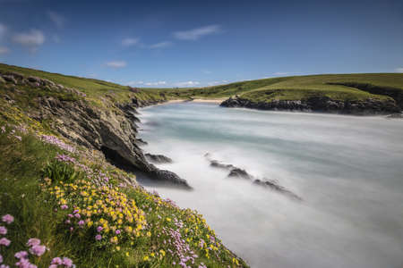 A frozen river in the middle of a beautiful green field in Porth Joke Cove, Cornwall, UK