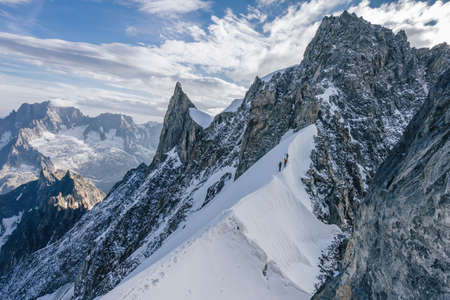 Climbers or alpinist on a knife sharp ridge of an alpine peak or summit of Aiguille du Rochefort. Alpine landscape and adventure climbing ascent. Reklamní fotografie
