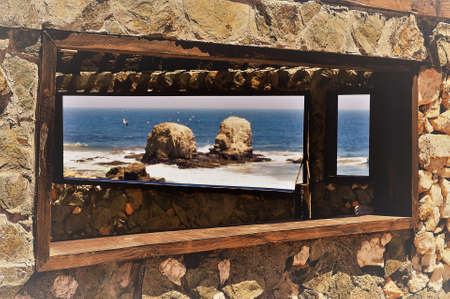 A beautiful view of two stones by the ocean visible through the window of a cottage 版權商用圖片