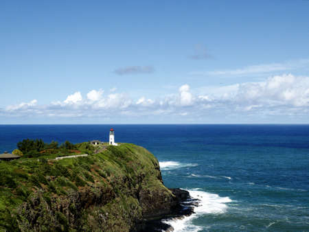 A beautiful view of a lighthouse on a grass covered cliff over the ocean under the cloudy sky