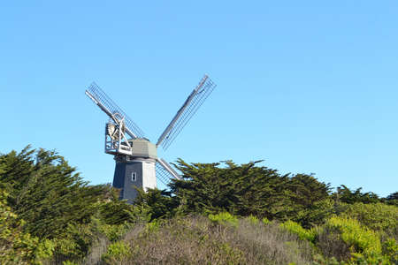 A grey windmill at Ocean Beach surrounded by greenery under a blue sky in San Francisco