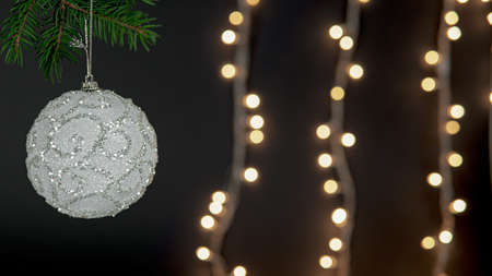 A white shiny Christmas ornament decoration on a pine branch with bokeh blurred lights in the background