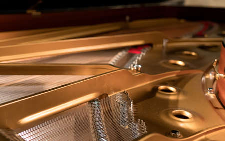 A closeup shot of the inner part of a golden piano with silver strings
