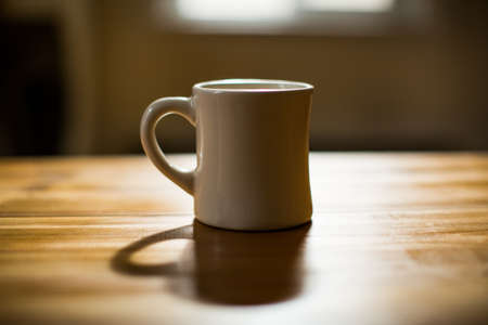 A white mug on a brown wooden table with a blurred background