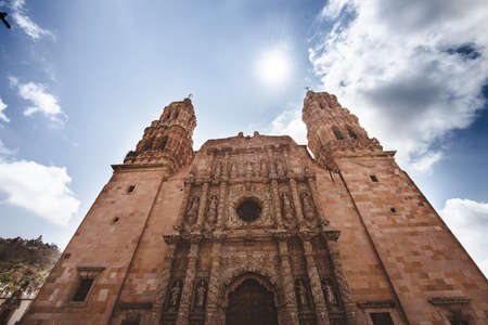 A low angle shot of a cathedral church with a blue cloudy sky in the background in Zacatecas Mexico Stock fotó