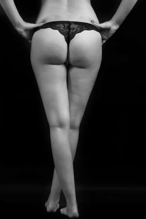 A vertical grayscale shot of a female in sexual underwear taken from the back