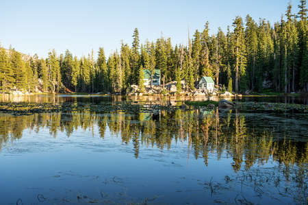A beautiful scenery of a forest surrounding a cabin reflecting in the Mosquito Lake
