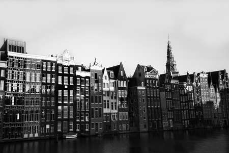 A grayscale shot of apartment buildings near the river under the clear sky