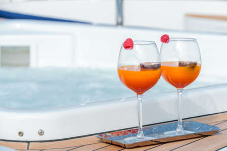 A closeup shot of two orange and red cocktails near the pool