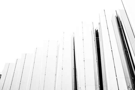 A greyscale low angle shot of a fence with glass panels under the white sky