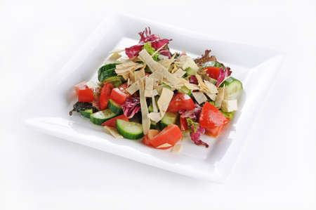 An isolated shot of a white plate with Greek salad - perfect for a food blog or menu usage