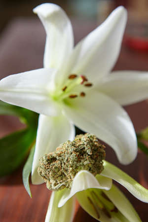 A vertical closeup shot of a piece of dry cannabis on a beautiful lily flower