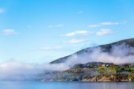 A scenery of smoke coming out of the mountains in Notodden, Telemark, Norway