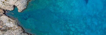 A high angle panoramic shot of a lot of rock formations in the ocean - great for a cool background