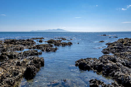 A high angle shot of rock formations in the water of Pukerua Bay in New Zealand