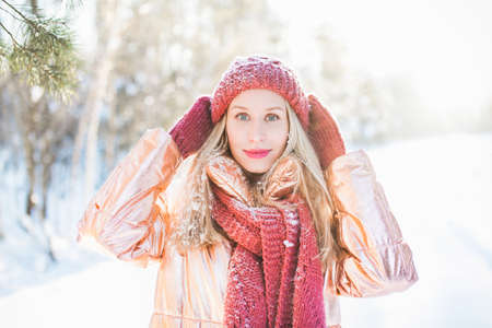 A beutiful blonde female with green eyes with snowflakes on her hair and red hat on a winter day Stock Photo