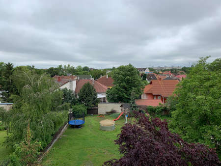 A landscape of a neighbourhood with a playground surrounded by greenery under a cloudy sky