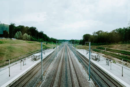 A high angle shot of the railway in a train station surrounded by grass covered fields and trees Stockfoto