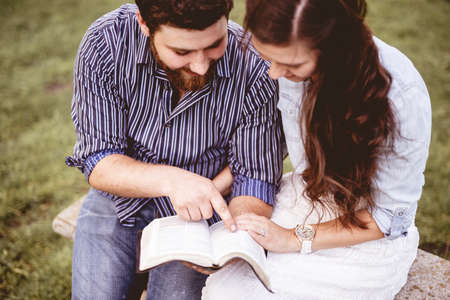 An overhead shot of a couple sitting on a bench and reading the bible with a blurred background