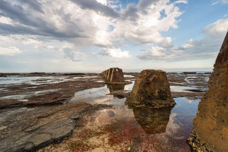 A beautiful shot of a brown rock formation surrounded by the ocean water under the cloudy sky Imagens