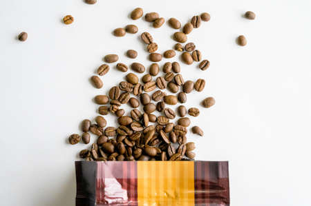 An overhead shot of coffee beans spilling out of the bag on white surface