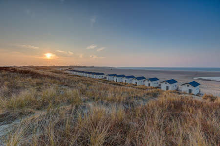 A high angle shot of similar cottages with blue roofs on the shore in Vrouwenpolder, Netherlands