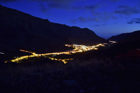The Gran Canaria surrounded by mountains and lights under a blue sky during the evening