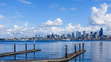 A wooden pier over a sea with the city of Seattle, USA under the beautiful clouds in the background