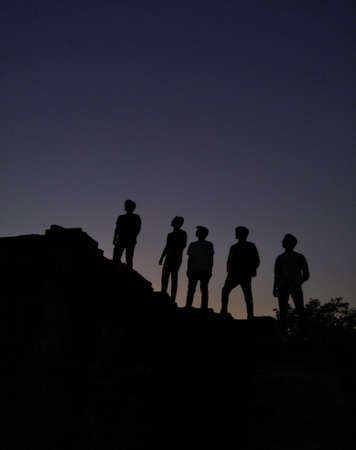 A vertical shot of silhouettes of people standing on a hill under the beautiful night sky