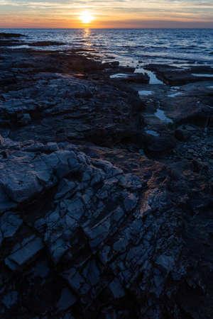 A vertical shot of rock formations at the shore of the Adriatic sea in Savudrija, Istria, Croatia