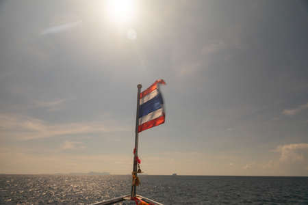 A beautiful shot of the flag of Thailand attached to the board of the boat in the ocean on a sunny day