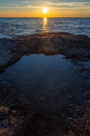 A vertical shot of the sunset over rock formations in the Adriatic sea in Savudrija, Istria, Croatia