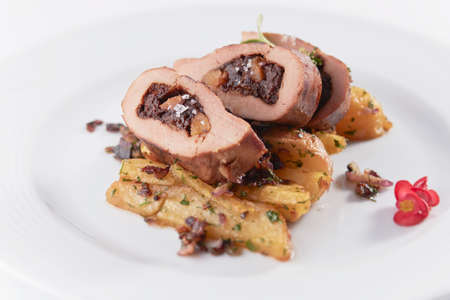 A closeup shot of stuffed pork with grilled potatoes in a white plate
