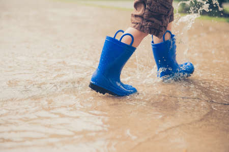 A closeup shot of the legs of a boy in blue rubber boots splashing in a puddle