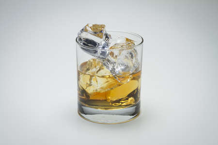 A closeup shot of a glass with whiskey and icecube on a white surface - great for a blog