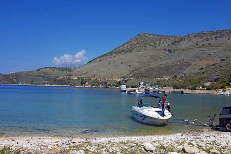 PORTO PALERMO, ALBANIA - Apr 14, 2017: Porto Palermo, Albania, has a marina for small boats. In the foreground: a group of people has just launched  a boat on to the water, from a trailer.