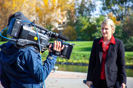 MONTREAL, CANADA - Oct 16, 2010: Montreal, Quebec / Canada - October 16 2010: Reporter Wearing a Red Clothes is Holding a Microphone in her Hand for Recording a TV News Story