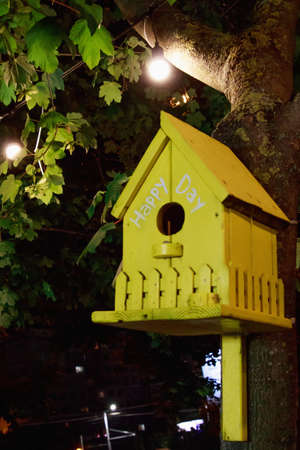 A vertical shot of a yellow birdhouse hanging on the tree with green leaves