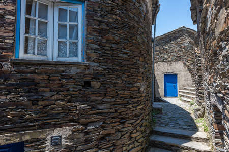 An alley surrounded by stone buildings under sunlight in Piodao Village in Portugal