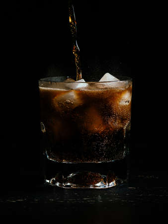A vertical shot of coke being poured in a glass full of ice on a black background Stock fotó